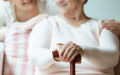 Senior woman holding her hands with painted nails on wooden walking stick