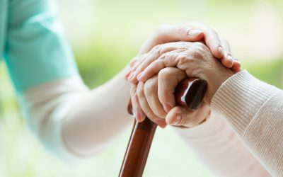 Nurse in apron comforting elder lady by touching her hands